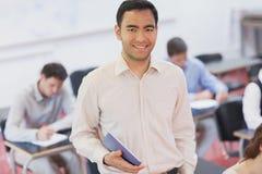 Rozochocony męski nauczyciel pozuje w jego sala lekcyjnej trzyma pastylkę Fotografia Stock