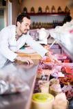 Rozochocony męski sklepowy asystent demonstruje kiełbasy w masarce Zdjęcia Stock