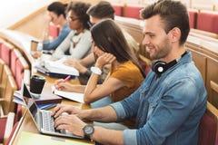 Rozochocony męski uczeń pisać na maszynie na laptopie Obrazy Royalty Free