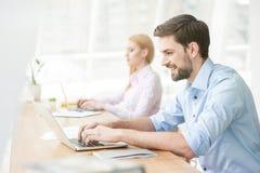 Rozochocony męski uczeń pracuje na komputerze Fotografia Royalty Free