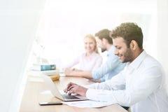 Rozochocony męski uczeń pracuje na komputerze Obraz Royalty Free