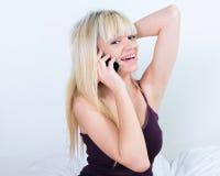 Rozochocony młodej dziewczyny telefonowanie, obsiadanie w łóżku i Obraz Stock