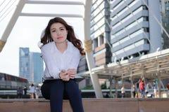 Rozochocony młody Azjatycki bizneswomanu obsiadanie na schody po pracy i pozytywnego spojrzenia przy miastowym budynku tłem Zdjęcie Stock
