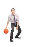 Rozochocony młody biznesmen bawić się koszykówkę Obrazy Stock