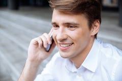 Rozochocony młody biznesmen opowiada na telefonie komórkowym zdjęcie stock