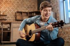 Rozochocony młody człowiek bawić się gitarę i ono uśmiecha się Obraz Stock