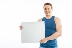 Rozochocony młody facet pokazuje pustego billboard obraz stock