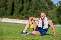 Rozochocony młody męski biegacz jest odpoczynkowy na trawie Obraz Royalty Free