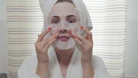 Rozochocony młody womanlooking w kamerze stosuje szkotową maskę na jej twarzy w łazience Śliczna dziewczyna z różnym zdjęcie wideo