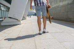 Rozochocony męski deskorolkarz ma spacer outdoors Fotografia Stock