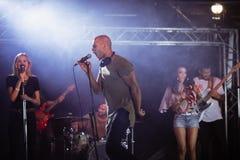 Rozochocony męski piosenkarz z muzykami wykonuje podczas festiwalu muzyki Obraz Royalty Free