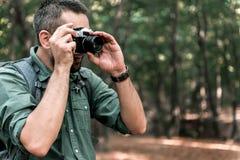 Rozochocony męski turysta bierze fotografie w lesie Zdjęcie Royalty Free