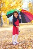 Rozochocony małej dziewczynki dziecko z kolorowym parasolem w jesieni zdjęcie royalty free
