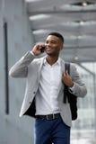 Rozochocony młody człowiek opowiada na telefonie komórkowym Fotografia Royalty Free