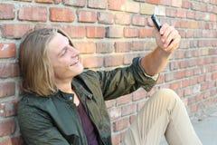 Rozochocony nastolatek bierze śmiesznych selfies z jego telefonem komórkowym zdjęcia stock