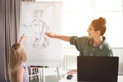 Rozochocony nauczyciel i dzieciak pokazuje na wizerunku robot obraz royalty free