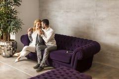 Rozochocony pary obsiadanie w kanapie w domu obraz royalty free