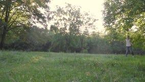 Rozochocony pies łapie prosto naprzeciw kamery zwolnione tempo, że dziewczyna treser stoi na zielonym gazonie zbiory wideo