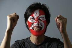 Rozochocony portret mężczyzna z flagą Hong kong malował na jego twarzy na popielatym tle Pojęcie sport zdjęcie royalty free