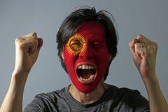 Rozochocony portret mężczyzna z flagą Kirgistan malował na jego twarzy na popielatym tle obraz royalty free