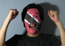 Rozochocony portret mężczyzna z flagą Trinidad i Tobago malował na jego twarzy na popielatym tle obrazy stock
