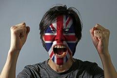 Rozochocony portret mężczyzna z flagą Union Jack malował na jego twarzy na popielatym tle zdjęcia stock