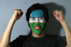 Rozochocony portret mężczyzna z flagą Uzbekistan malował na jego twarzy na popielatym tle zdjęcie royalty free