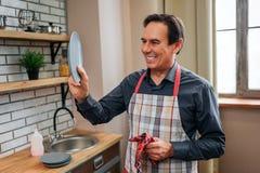 Rozochocony pozytywny mężczyzna samodzielny w kuchni On stary talerz i spojrzenie przy nim mężczyzna uśmiech Suszył mnie z ręczni obrazy royalty free