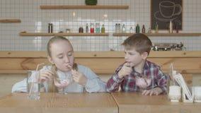 Rozochocony preteen żartuje łasowanie lody w kawiarni zbiory