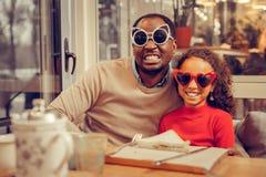 Rozochocony promieniejący ojciec i córka jest ubranym śmiesznych szkła obraz royalty free