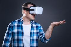 Rozochocony przystojny mężczyzna trzyma wirtualnego przedmiot Fotografia Stock