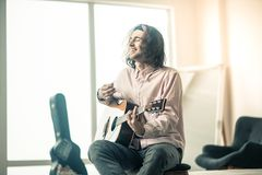 Rozochocony przystojny młody gitarzysty obsiadanie w jaskrawym pokoju obraz royalty free