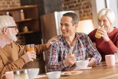 Rozochocony rodzinny cieszy się śniadanie w kuchni obraz royalty free