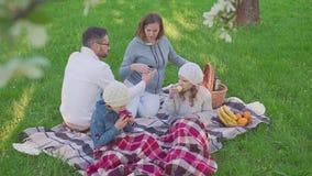 Rozochocony rodzinny obsiadanie na trawie podczas pinkinu w parku, wszystko śniadanie tam jest koszem z posiłkiem świeży zbiory