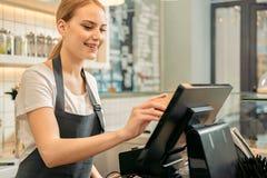 Rozochocony sklepowy asystent używa cyfrowego przyrząd dla zapłaty Obrazy Stock