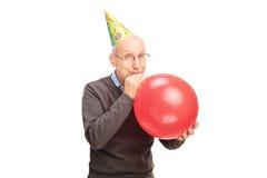 Rozochocony starszy dmuchanie w górę balonu - Fotografia Stock