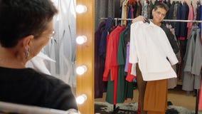 Rozochocony starszy kobiety mienia ubrań przodu lustro podczas gdy robiący zakupy w ubrania sklepie Szczęśliwy kobiety wybierać n zbiory