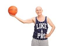 Rozochocony starszy mężczyzna trzyma koszykówkę Obraz Stock