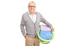 Rozochocony starszy mężczyzna trzyma pralnianego kosz zdjęcie royalty free