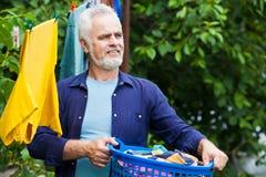 Rozochocony starszy mężczyzna z pralnianym koszem plenerowym fotografia stock