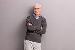 Rozochocony starszy opierać przeciw szarej ścianie Zdjęcie Royalty Free