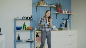 Rozochocony szczęśliwy dziewczyna taniec, śpiew w kuchni i podczas gdy surfujący ogólnospołecznych środki na jej smartphone w ran zbiory wideo