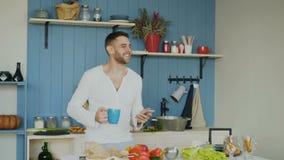 Rozochocony szczęśliwy mężczyzna taniec, śpiew w kuchni i podczas gdy surfujący ogólnospołecznych środki na jego smartphone w ran zdjęcie wideo