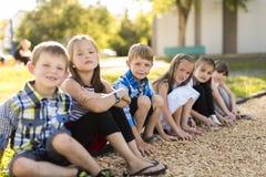 Rozochocony szkolnego wieka dzieci bawią się na boisko szkole Obrazy Royalty Free