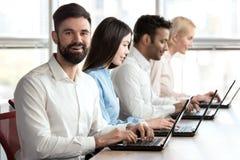 Rozochocony uśmiechnięty brodaty caucasian mężczyzna w biurze Zdjęcia Stock