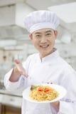 Rozochocony uśmiechnięty szef kuchni pokazuje przygotowanego jedzenie w kuchni Obraz Royalty Free