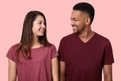 Rozochocony wieloetniczny pary spojrzenie szczęśliwie przy each inny, ono uśmiecha się delikatnie, cieszy się wolnego czas wpólni fotografia stock