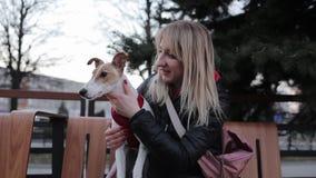 Rozochocony zwierzę domowe właściciel z jej psem siedzi na ławce i pozować kobieta pieści psa zbiory wideo