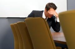 Rozpaczający biznesmena obsiadanie w biurze obraz stock