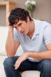 Rozpaczający mężczyzna obsiadanie na kanapie zdjęcia stock